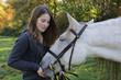 mädchen füttert weißes Pferd auf der weide