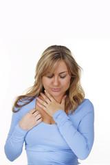 Junge Frau fasst sich an den Hals bei Halsweh