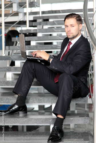 A businessman sitting on stairs smiling with a laptop computer