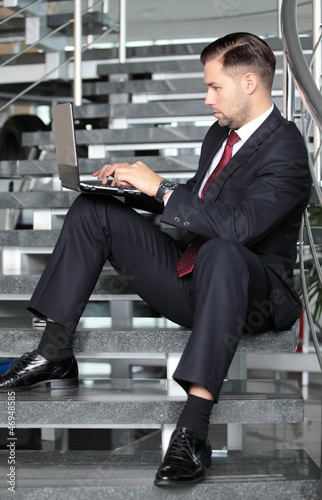 Handsome businessman sitting on the stairs and using his laptop