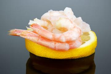 Stack of shrimps on lemon, glossy background