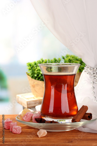 glass of Turkish tea and rahat lokum, on wooden table