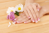 Woman hands with french manicure and flowers - 46950385