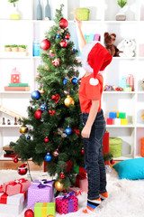 Little boy in Santa hat decorates Christmas tree in room