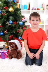 Little boy sits near Christmas tree