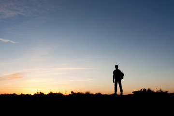 Silhouette of a mountaineer enjoying the sunset view