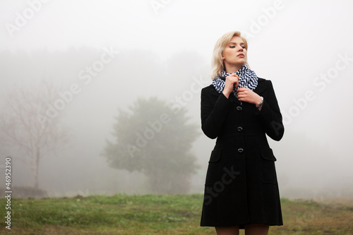Young woman walking in an autumn foggy field