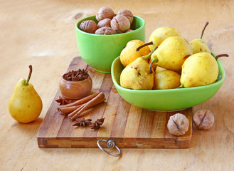 Pears,  walnuts, cinnamon and ginger on a wooden table