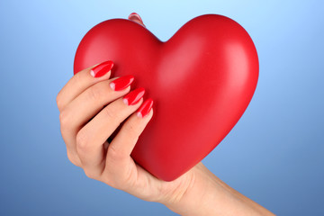 Red heart in woman's hand on color background