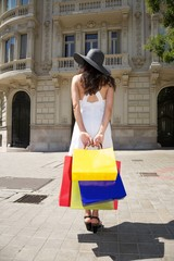 white dressed woman holding shopping bags