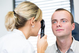 optometry concept - handsome young man having her eyes examined