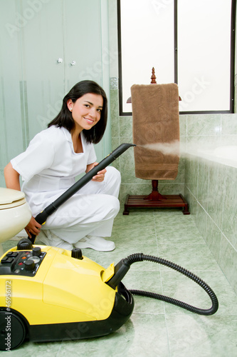 Young woman steam cleaning the bathroom