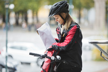 Female Cyclist Putting Package In Courier Bag