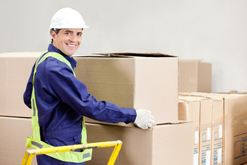 Foreman Holding Cardboard Box in Warehouse