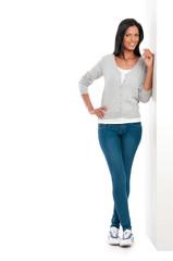 Happy latin girl standing on wall