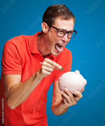 Portrait Of  Man With Piggy Bank Inserting A Coin