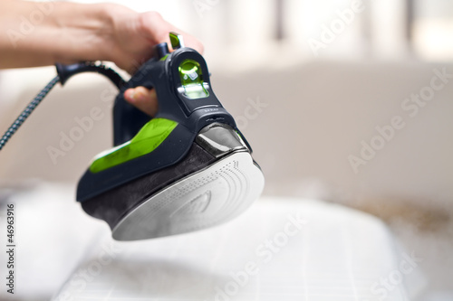 Woman ironing laundry with new ecologycal iron
