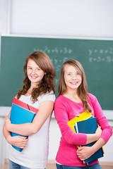zwei schülerinnen stehen im klassenzimmer