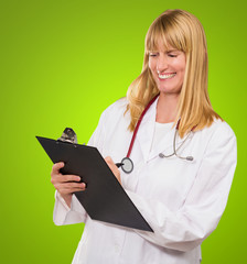 Portrait Of Happy Doctor Writing On Clipboard
