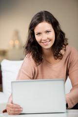 frau schreibt abends am laptop