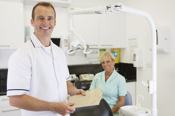 A male dentist and female nurse in a dental surgery