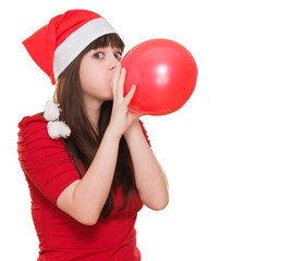 woman wearing a christmas hat and blowing a balloon