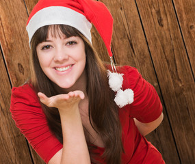 woman wearing a christmas hat and blowing a kiss