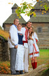 Two young couples in Ukrainian style clothing posing outdoors