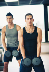 Two young men exercising with dumbbells in the gym.