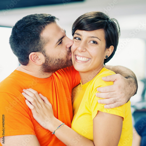 Young couple embracing and kissing at the gym.