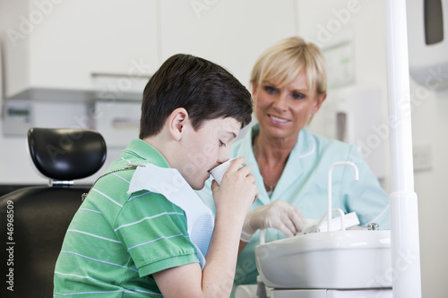A young boy at the dentist rinsing his mouth