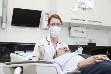 A female dentist examining a male patients teeth