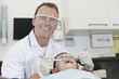 A male dentist working on a young boy patients teeth
