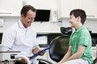 A male dentist talking to a young boy patient