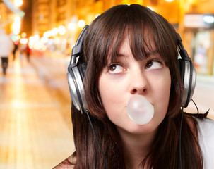 portrait of young woman listening to music with bubble gum at ni