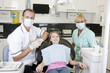 A dentist and dental nurse with a young girl patient