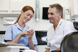A dentist and dental nurse looking at a dental cast