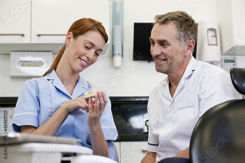 A dentist and dental nurse looking at a dental cast
