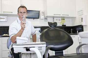 A male dentist in his surgery testing a dental drill