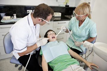 A young boy patient having dental treatment, looking scared