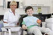 A young boy at the dentist holding an apple