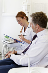 A female dentist discussing dental records with a male patient