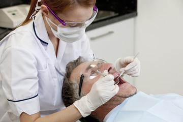 A female dentist examining a male patients teeth, close up