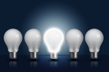 Incandescent light bulb in a row with middle light bulb on