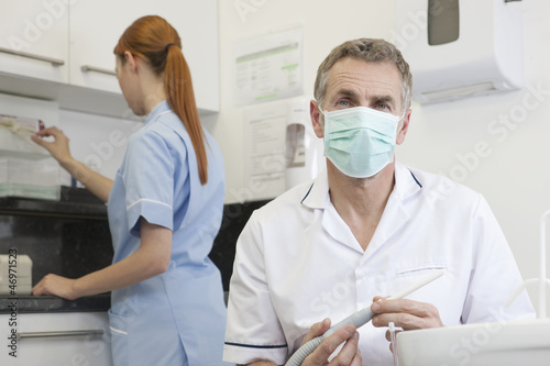 A male dentist and female dental nurse in a dental surgery