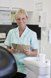 A female dental nurse holding patient dental records