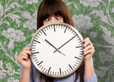 Woman Holding Clock With Squinted Eyes