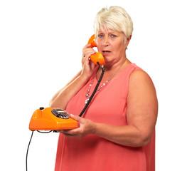 Portrait Of A Senior Woman Holding A Retro Phone