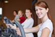 Gruppe trainiert im Fitnesscenter am Crosstrainer