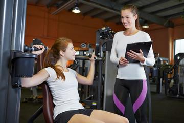 Frau an Schulterpresse mit Fitnesstrainerin